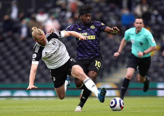 Fulham's Tim Ream (left) and Newcastle United's Allan Saint-Maximin (right) battle for the ball during the Premier League match at Craven Cottage, London. Picture date: Sunday May 23, 2021.