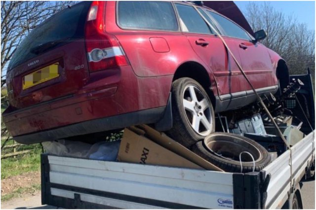 A driver who was pulling a trailer that had a car precariously perched on top of scrap metal and not secured in place.