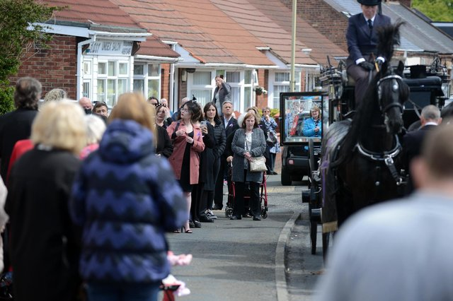 Funeral procession for Monkton Village store Gladys Stonehouse as mourners gather on the street.