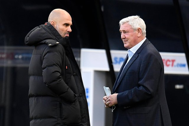 Steve Bruce, manager of Newcastle United, interacts with Pep Guardiola, Manager of Manchester City.
