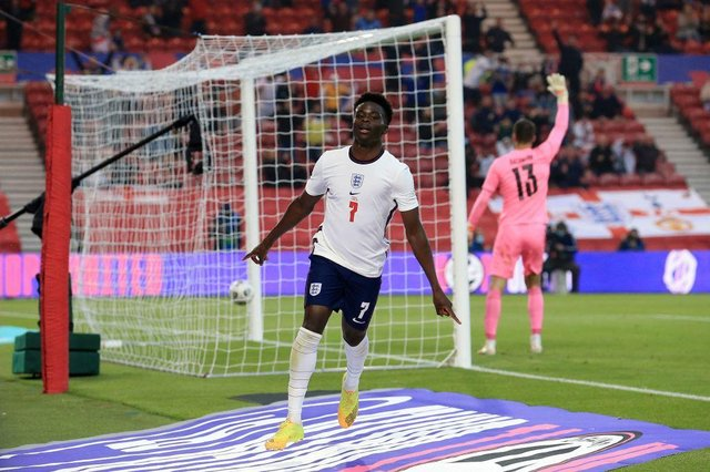 England's defender Bukayo Saka celebrates scoring the opening goal during the international friendly football match between England and Austria at the Riverside Stadium.