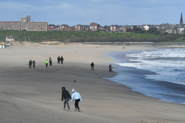 Walkers on the beach at South Shields this morning as blustery conditions hit the region.