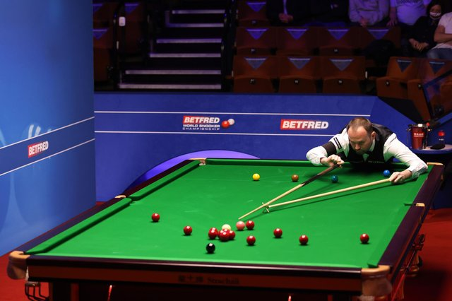 Mark Joyce lines up a shot during the Betfred World Snooker Championships 2021. Picture by PA