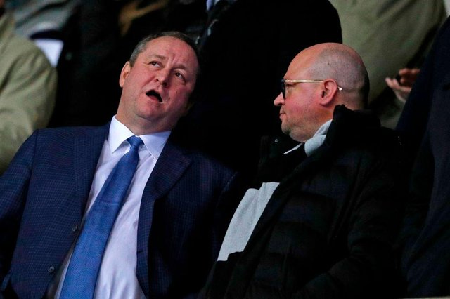 Newcastle United's English owner Mike Ashley (L) chats with director Lee Charnley (R) in the crowd ahead of the FA Cup fourth round replay football match between Oxford United and Newcastle United at the Kassam Stadium in Oxford, west of London, on February 4, 2020.