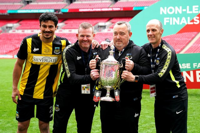 Hebburn Town manager Kevin Bolam (second right) celebrates with Angelos Eleftheriadis (left), coaches Michael Mulhern and Jason Miller (right) with the Buildbase FA Vase 2019/20 Trophy after victory in the Final at Wembley Stadium.