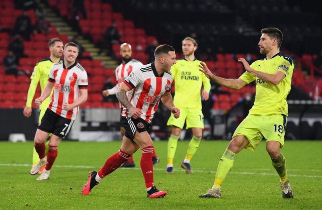 Billy Sharp of Sheffield United (l) clashes with Federico Fernandez after scoring the winning goal from the penalty spot during the Premier League match between Sheffield United and Newcastle United at Bramall Lane on January 12, 2021 in Sheffield, England.