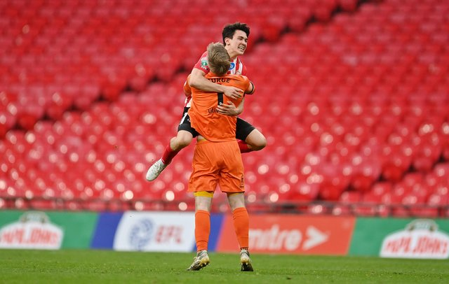 Lee Burge of Sunderland celebrates victory with teammate Luke O'Nien following the Papa John's Trophy Final match between Sunderland and Tranmere Rovers.