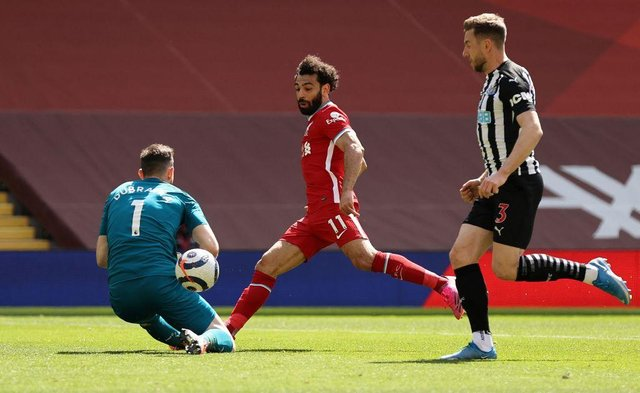 Newcastle United's Slovakian goalkeeper Martin Dubravka (L) saves a shot from Liverpool's Egyptian midfielder Mohamed Salah (C) during the English Premier League football match between Liverpool and Newcastle United at Anfield in Liverpool, north west England on April 24, 2021.