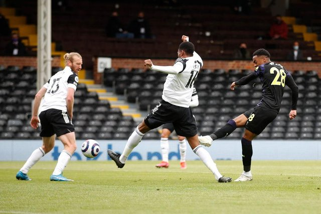 Joe Willock of Newcastle United scores their sides first goal whilst under pressure from Tosin Adarabioyo of Fulham during the Premier League match between Fulham and Newcastle United at Craven Cottage on May 23, 2021 in London, England.