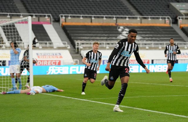 Joe Willock of Newcastle United celebrates after scoring their sides third goal, missing from the penalty spot but scoring the rebound during the Premier League match between Newcastle United and Manchester City at St. James Park on May 14, 2021 in Newcastle upon Tyne, England.