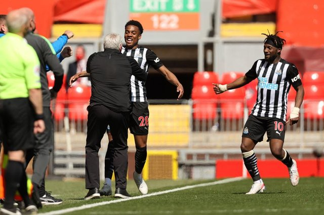 Joe Willock of Newcastle United celebrates with Steve Bruce, Manager of Newcastle United and Allan Saint-Maximin after scoring their side's first goal during the Premier League match between Liverpool and Newcastle United at Anfield on April 24, 2021 in Liverpool, England.