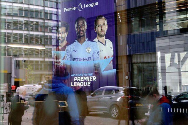 Members of the media are reflected in the glass at the headquarters of the English Premier League in London on March 13, 2020.