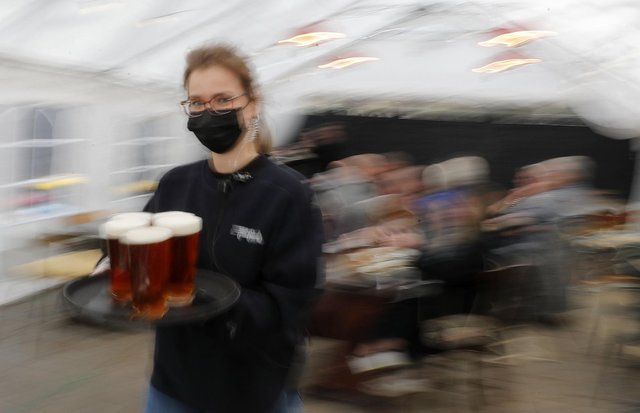 A waitress carries pints under a marquee on Monday, April 12, 2021 (AP Photo/Frank Augstein)