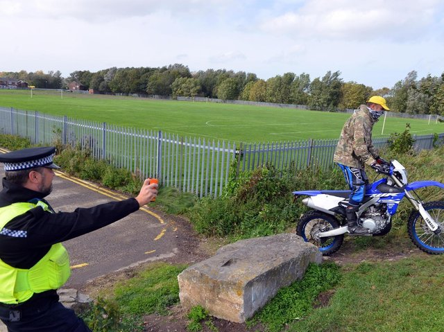 A Northumbria Police officer tests out a DNA spray as Pc Mike 'Spike' Fisher rides by.
