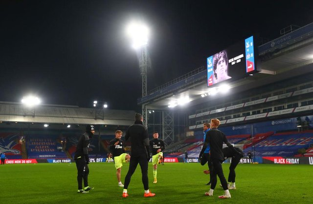 Elliot Anderson, centre, warms up with Newcastle United's substitutes at Selhurst Park.