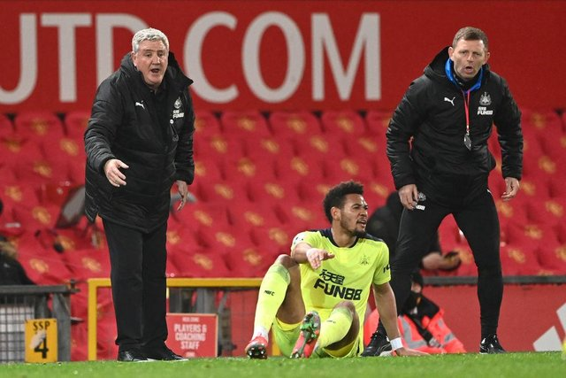 Newcastle manager Steve Bruce (l) and coach Graeme Jones look on as 'striker Joelinton reacts after going to ground during the Premier League match between Manchester United and Newcastle United at Old Trafford on February 21, 2021 in Manchester, England.