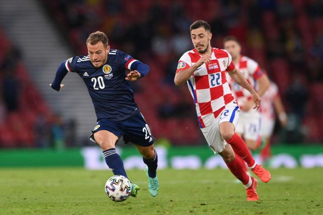 Ryan Fraser of Scotland runs with the ball as he is closed down by Josip Juranovic of Croatia during the UEFA Euro 2020 Championship Group D match between Croatia and Scotland at Hampden Park on June 22, 2021 in Glasgow, Scotland.