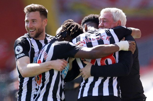 Joe Willock is embraced by Steve Bruce and his team-mates after scoring at Anfield.