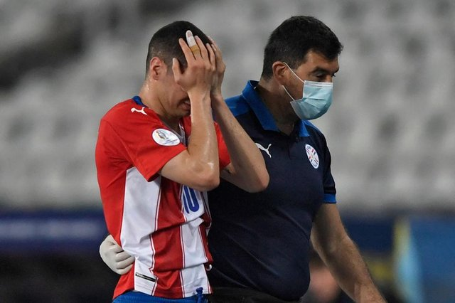 Miguel Almiron leaves the field after suffering an injury against Uruguay.