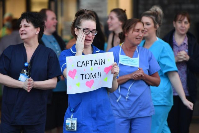 An NHS staff member wipes her eyes as she holds a sign to thank British veteran Captain Tom Moore who raised over £13 million for the NHS (Photo: ANTHONY DEVLIN/AFP via Getty Images)