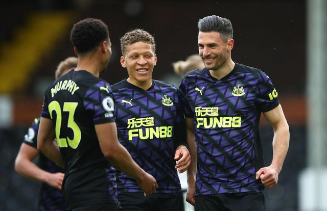 Fabian Schar of Newcastle United celebrates with Dwight Gayle and nu after scoring his sides second goal during the Premier League match between Fulham and Newcastle United at Craven Cottage on May 23, 2021 in London, England.