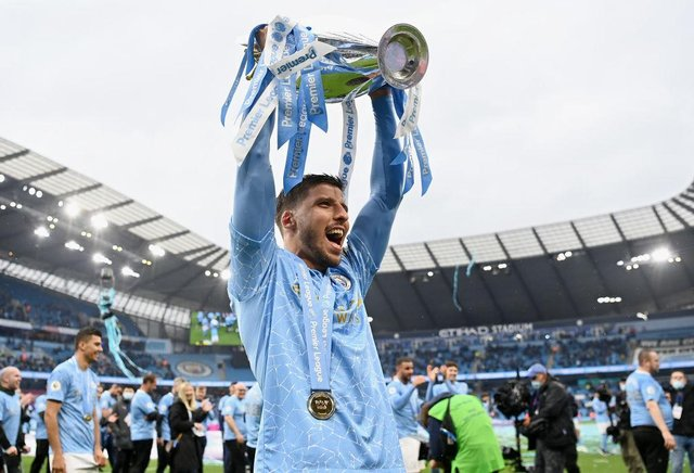 Ruben Dias of Manchester City celebrates with the Premier League Trophy as Manchester City are presented with the Trophy as they win the league following the Premier League match between Manchester City and Everton at Etihad Stadium on May 23, 2021 in Manchester, England.