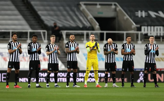Players of Newcastle United participate in a minute of applause in memory of former Newcastle United player Glenn Roeder during the Premier League match between Newcastle United and Aston Villa at St. James Park on March 12, 2021 in Newcastle upon Tyne, England.